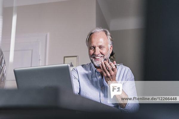 Porträt des lächelnden reifen Mannes mit Laptop und Handy zu Hause