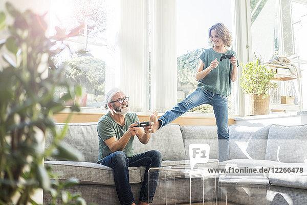 Glückliches reifes Paar auf der Couch zu Hause beim Videospielen