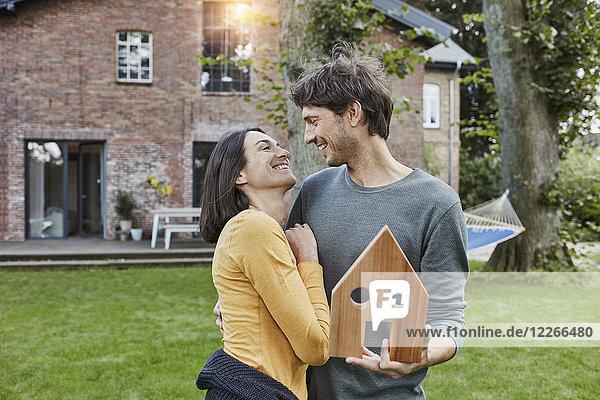 Ein glückliches Paar im Garten ihres Hauses als Modell