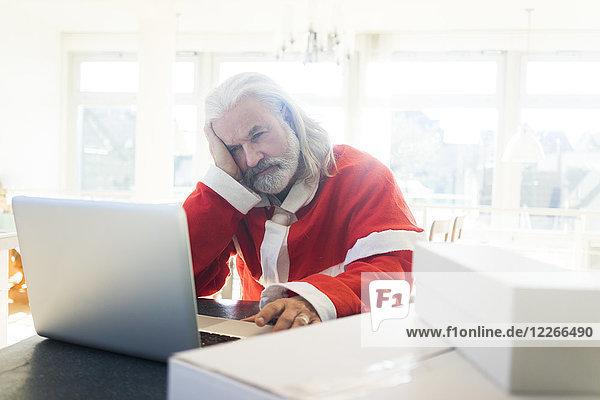 Frustrierte Weihnachtsmann mit Laptop zu Hause