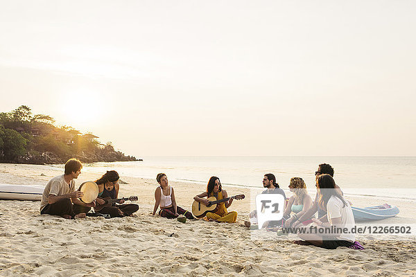 Thailand  Koh Phangan  group of people sitting on a beach with guitar at sunset