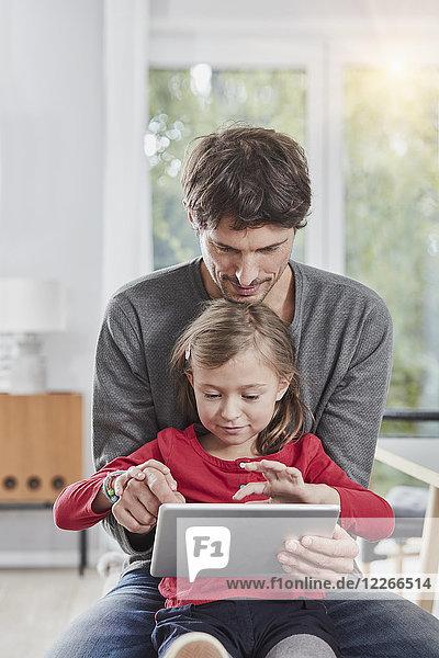 Vater und Tochter benutzen die Tablette gemeinsam zu Hause.