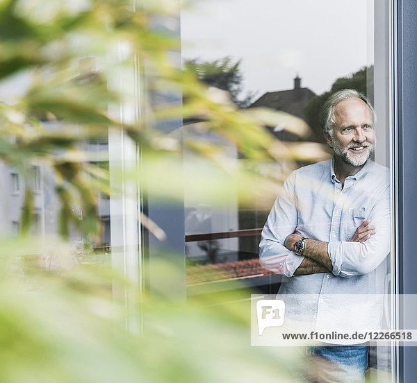 Lächelnder reifer Mann  der aus der Terrassentür schaut