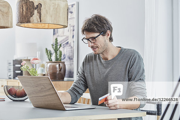 Mann hält eine Karte mit Laptop auf dem Tisch zu Hause