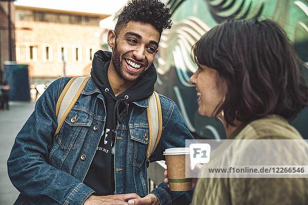 Fröhlicher junger Mann und Frau mit Kaffee im Gespräch in der Stadt