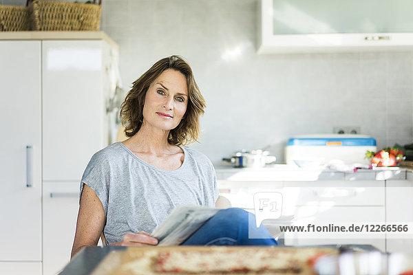 Porträt einer Frau mit Zeitung in der Küche zu Hause