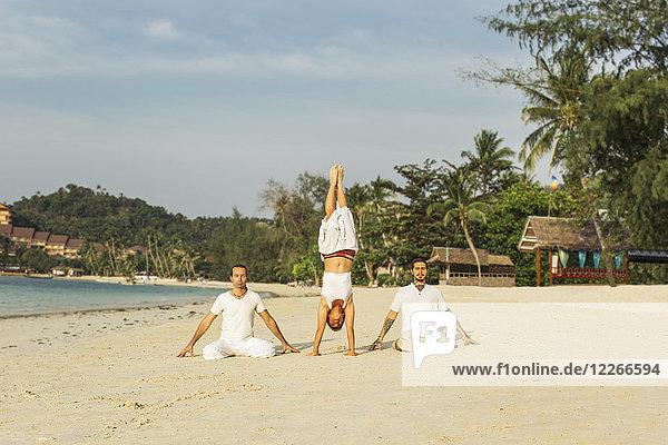 Thailand  Koh Phangan  drei Leute beim Yoga am Strand