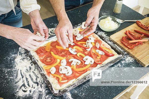 Nahaufnahme eines Paares bei der Zubereitung einer Pizza in der heimischen Küche