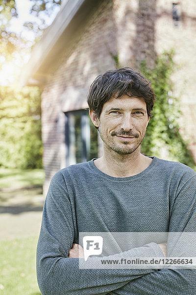 Porträt eines selbstbewussten Mannes vor seinem Haus