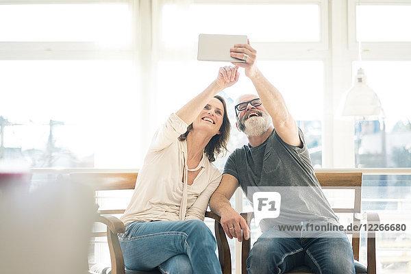 Glückliches reifes Paar  das zu Hause auf Stühlen sitzt und Tabletten benutzt