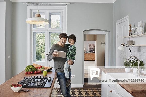 Glücklicher Vater und Sohn mit Tablette in der Küche zusammen
