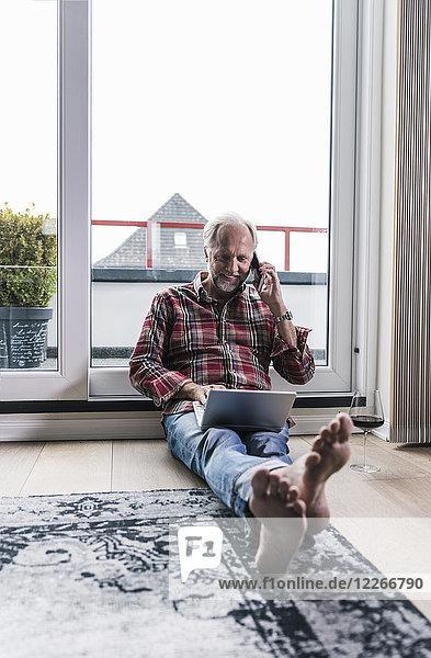 Barfuss-Mann am Telefon entspannt auf dem Boden zu Hause mit Laptop und einem Glas Rotwein