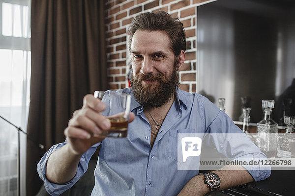 Porträt eines lächelnden Mannes mit einem Glas Whiskey zu Hause