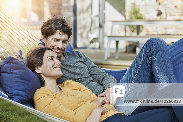 Lächelndes Paar in der Hängematte im Garten des Hauses liegend
