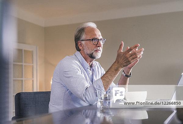 Erwachsener Mann mit Laptop  der zu Hause am Tisch sitzt