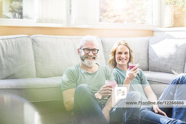 Glückliches reifes Paar mit gesunden Getränken im Wohnzimmer zu Hause