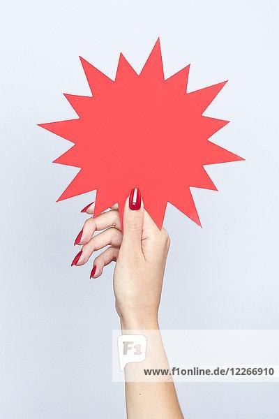 Nahaufnahme der Frauenhand mit einem leeren gezackten Schild