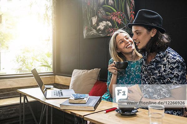 Künstlerpaar sitzend im Café und gemeinsam Spaß habend