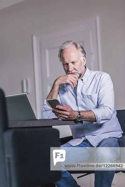Erwachsener Mann am Tisch sitzend mit Laptop beim Blick aufs Handy