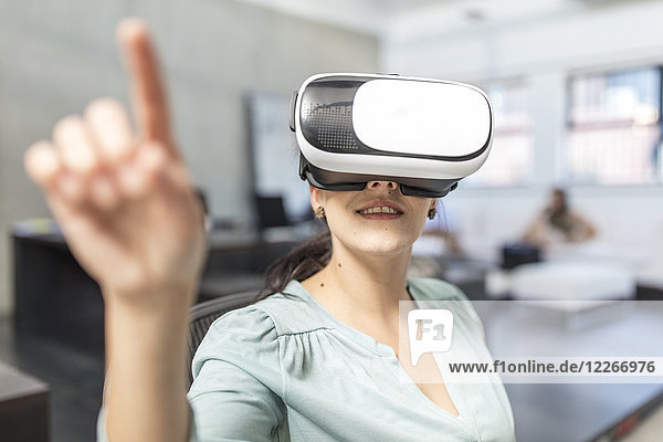 Woman wearing VR glasses in office