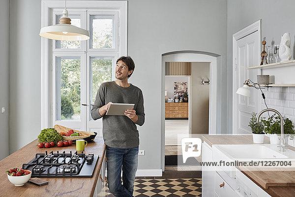 Mann mit Tablette in der Küche mit Blick auf die Deckenlampe