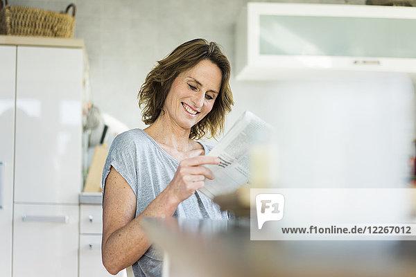 Lächelnde Frau beim Zeitungslesen in der Küche zu Hause