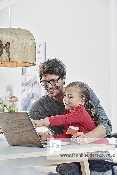 Glückliche Vater und Tochter mit einer Karte mit Laptop auf dem Tisch zu Hause