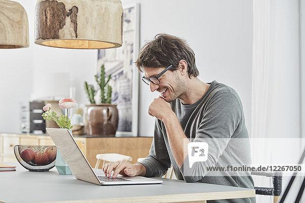 Lächelnder Mann mit Laptop auf dem Tisch zu Hause