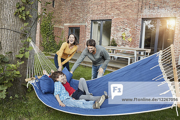Glückliche Familie beim Spielen in der Hängematte im Garten ihres Hauses