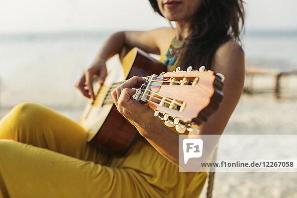 Thailand  Koh Phangan  Frau beim Gitarrespielen am Strand
