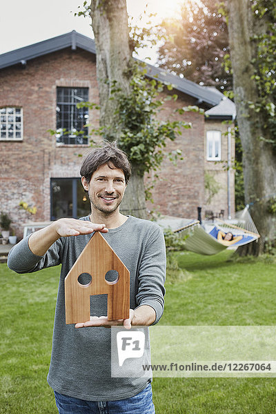 Porträt eines Mannes im Garten seines Hauses mit einer Frau im Hintergrund in der Hängematte.