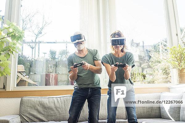 Erwachsenes Paar im Wohnzimmer zu Hause mit VR-Brille beim Videospielen