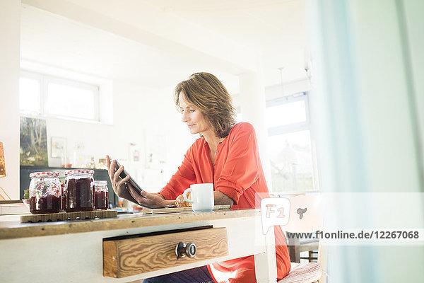Frau mit Tablette und hausgemachter Erdbeermarmelade zu Hause