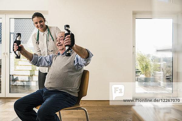 Junge Frau unterstützt älteren Mann bei einer Armübung