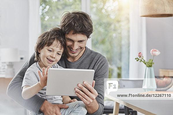 Glücklicher Vater und Sohn benutzen die Tablette zu Hause zusammen.