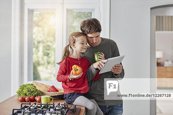 Vater und Tochter mit Paprika und Tablette in der Küche