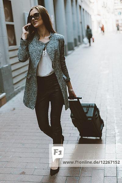 Junger Tourist am Telefon  der die Straße entlang geht.
