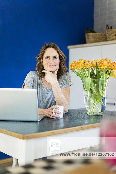 Porträt der lächelnden Frau mit Laptop in der Küche zu Hause