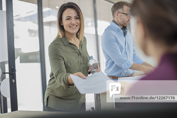 Smiling businesswoman in office handing over paper to colleague