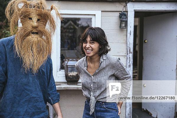 Mann mit lustiger Maske und Frau lachend