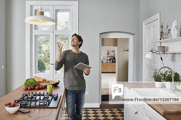 Glücklicher Mann mit Tablette in der Küche mit Blick auf die Deckenlampe