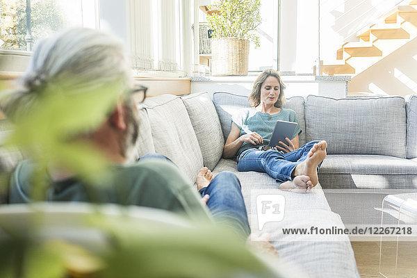 Ein reifes Paar entspannt sich zu Hause auf der Couch mit einer Frau  die eine Tablette hält.