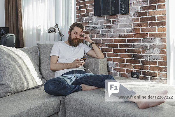 Man with cell phone relaxing on the couch at home