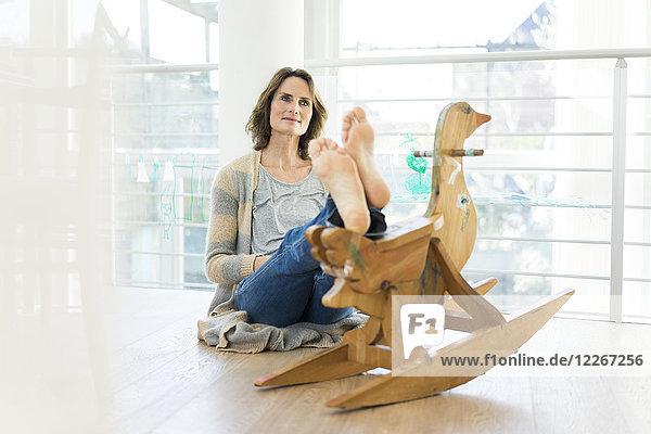 Barfußfrau auf dem Boden sitzend mit Holzspielzeug