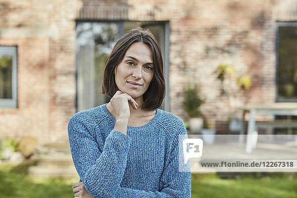 Porträt einer selbstbewussten Frau im Garten ihres Hauses