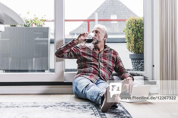 Barfuss-Mann entspannt sich zu Hause auf dem Boden und trinkt ein Glas Rotwein.