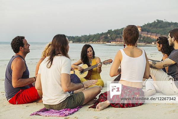 Thailand  Koh Phangan  Gruppe von Menschen am Strand mit Gitarre