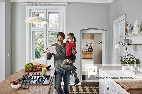 Glücklicher Vater und Tochter mit Paprika und Tablette in der Küche