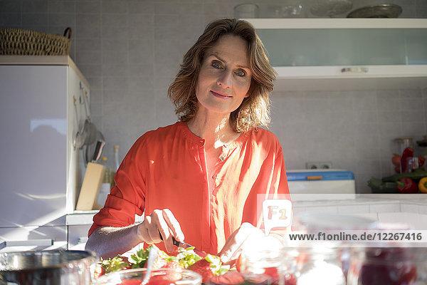 Porträt der Frau  die in der Küche zu Hause Erdbeermarmelade herstellt.