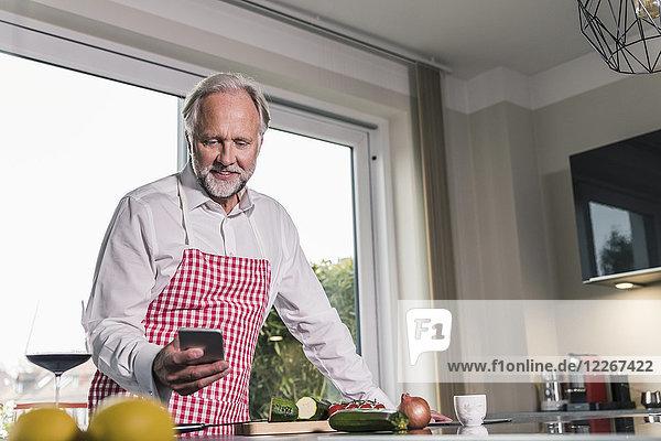 Portrait des reifen Mannes in der Küche mit dem Handy